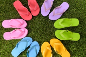 Circle of flip flops on grass.